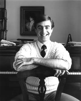 David Earl seated on a chair at the piano and smiling at the camera
