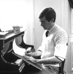 David seated at the piano while composing.