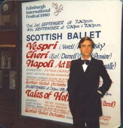 David Earl stands in front of a poster advertising the Scottish Ballet production of his ballet Cheri